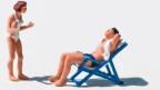 Strandszene: Ein Mann liegt im Liegestuhl, während eine Frau auf ihn einspricht.