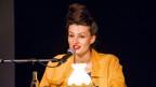 Eine Frau mit einem Buch in den Händen, vor einem Mikrofon