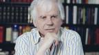 Ein älterer, grauhaariger Mann mit gestreiftem Hemd vor einem Bücherregal