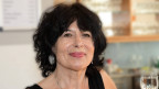 Frau mit mittellangen, schwarzen Haaren und rotem Lippenstift lächelt in die Kamera