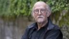 Älterer Mann mit längeren grauen Haaren, schwarzem Hemd und runder Brille