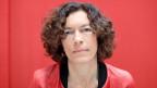Frau mit kinnlangen braunen Haaren vor rotem Hintergrund