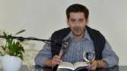 Mann mittleren Alters sitzt vor Mikrophon und liest aus einem Buch