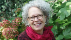 Frau mit grauen gelockten Haaren und runder Brille