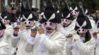 Menschen mit Masken und Hüten spielen Piccolo-Querflöte.