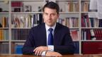 Gottfried Locher sitzt im Anzug an einem Schreibtisch