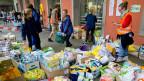 Freiwillige Helfer sortierenam Hauptbahnhof München Taschen mit Sachspenden.