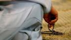 Eine nicht sichtbare Person hält eine Perlenkette in der Hand.