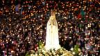 Fatima-Statue inmitten einer Menschenmenge, die Kerzen halten.
