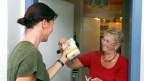 Eine jüngere Frau übergibt an der Wohnungstür einer älteren Frau eine Packung Mehl