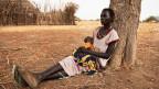 Eine Sudanesische Frau sitzt auf dem Boden und lehnt sich an einen Baum, in den Ärmen hält sie ein Säugling.