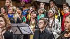 Frauen in bunter Kleidung singen in einem Chor in einer Kirche.