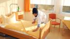 Türkische Altenpflegerin bettet das Bett in einem Altersheim