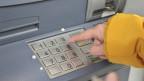Jemand lässt Geld aus einem Bankomat