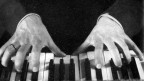 Schwarz-weiss Foto von Händen, die auf einem Klavier spielen.