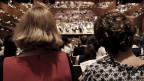 Zwei Frauen von hinten, die auf ein Orchester schauen.