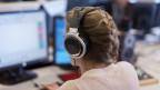 Eine Frau vor einem Computer. Sie hat Kopfhörer auf.