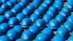 Blauhelme liegen auf dem Boden, dicht an dicht aneinandergereiht.