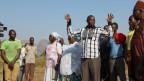 Ein afrikanischer Mann spricht mit erhobenen Armen zu einer Menschengruppe.