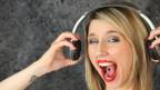 Eine Frau mit offenem Mundk, roten Lippen und Kopfhörern.