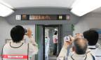 Die Innenansicht eines Zuges: Passagiere fotografieren die Geschwindigkeitsanzeige, die 300 Stundenkilometer anzeigt.