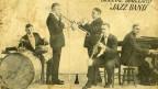 """Eine alte AUfnahme von fünf Musikern. Zu Lesen ist: """"Original Dixieland Jazz Band""""."""