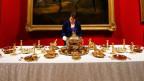Frau richtet Tisch mit goldenem Gedeck an.