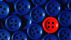 Lauter blaue Knöpfe, dazwischen ein einzelner roter.