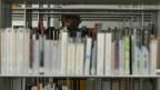 Ein Gesicht ragt zwischen Bibliotheksregalen hindurch.
