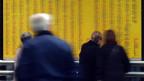 Menschen stehen vor gelben Abfahrtstafeln der SBB.