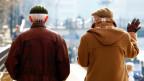 Zwei ältere Männer von hinten fotografiert. Sie gehen eine Strasse runter.