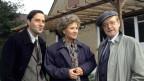 Ein älterer Mann, eine ältere Dame und ein junger Mann stehen nebeneinander vor einem Haus und posieren für die Kamera.