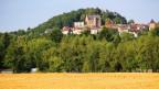 Foto von einem Dorf auf einem Hügel mit Burg