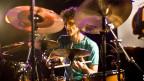Ein Mann mit Locken spielt Schlagzeug.