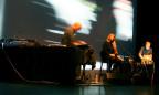 Eine Frau mit längeren, rötlichen Haaren singt in ein Mikrofon, Musiker stehen um sie herum.