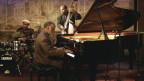 Eine dreiköpfige Band: Schlagzeuger, Pianist und Kontrabassist
