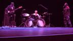 Ein Bassist, ein Saxofonist und ein Drummer spielen auf einer beleuchteten Bühne.
