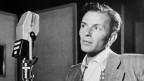 Ein junger Mann steht ohne zu singen vor einem Mikrophon und hält den Kopf leicht schief.