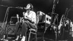 Schwarz-Weiss Foto von Ry Cooder auf der Bühne. Er spielt Gitarre und singt.