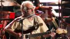 J.J. Cale mit Mikrofon und Gitarre sitzend auf einer Bühne
