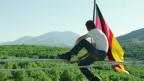 Mann mit Deutschlandfahne auf Gerüst vor Wald