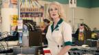 Frau im 50er Look hinter Ladenkasse