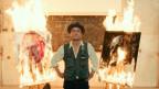 Mann mit Hut zwischen zwei brennenden Bildern