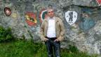 Ein Mann steht vor einer Felswand, die mit Wappen bemalt ist.