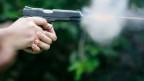 Eine Hand hält eine Pistole, aus der es raucht.