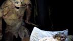 Monster-Puppe macht sich mit Messer über schlafenden Mann her.