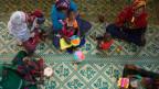 Kinder und Mütter sitzen auf einem Teppich.