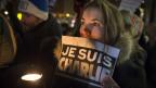 """Eine Frau hält ein Plakat mit der Aufschrift """"Je suis Charlie"""""""