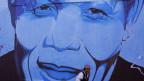 Ein Mann geht an einer Wand vorbei, an der eine grosse, blaue Wandmalerei mit dem Porträt von Nelson Mandela zu sehen ist.