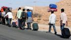 Eine Gruppe von Menschen wandert mit Gepäck der Strasse entlang.